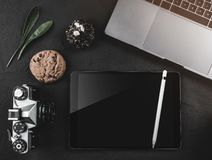 Laptop, digital tablet and photo camera, top view on a black desktop. Coffee break with sweets, top view Stock Photos