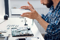 Laptop disassembling at electronic repair shop. Side view on bearded engineer separating computer from case. Electronic renovation, business, occupation Royalty Free Stock Photo