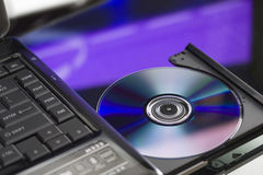 Laptop with a disk dvd. Close up. Royalty Free Stock Photography