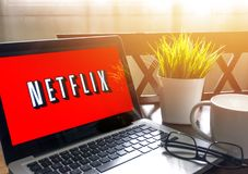 Laptop displaying Netflix word on wooden table Stock Image