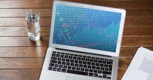 Laptop with document and glass of water on wooden table. Laptop with business document and glass of water on wooden table Royalty Free Stock Photo