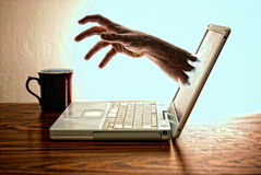 The laptop that drank coffee. Modern white norebook laptop computer sitting on desk with red coffee cup  with hand reaching out of screen for the coffee Stock Photo