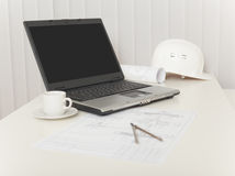 Laptop, drawings, helmet and compasses on table Stock Images