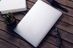 Laptop, dzienniczek, garnek roślina, widowiska i mądrze zegarek na drewnianym stole, Obrazy Stock