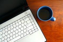 Laptop e uma caneca de café azul em uma tabela Fotografia de Stock