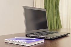 Laptop ein Adressbuch und ein Stift auf dem Tisch Lizenzfreie Stockbilder