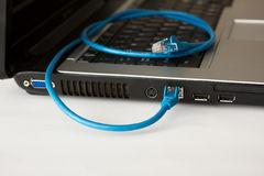 Laptop en blauwe voorzien van een netwerkkabel Royalty-vrije Stock Foto