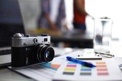Laptop en camera op het bureau, twee zakenlui die zich op de achtergrond bevinden Stock Fotografie
