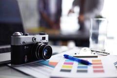 Laptop en camera op het bureau, twee zakenlui die zich op de achtergrond bevinden Stock Afbeeldingen