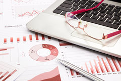 Laptop en de glazen met rode bedrijfsgrafieken, grafieken, onderzoeken Stock Foto