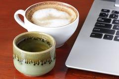 Laptop en een kop thee Stock Afbeeldingen