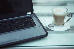 Laptop en een kop van koffie Stock Foto's