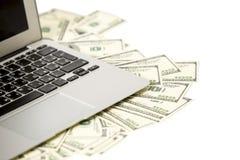 Laptop en geld Stock Afbeelding