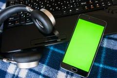 Laptop en hoofdtelefoonssmartphone met het groene scherm voor zeer belangrijke chrom Royalty-vrije Stock Foto