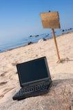 Laptop en houten teken op strand Royalty-vrije Stock Foto