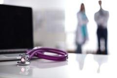 Laptop en medische stethoscoop op het bureau, artsen die zich op de achtergrond bevinden Stock Fotografie