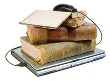 Laptop en oude boeken met weg stock foto