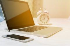 Laptop en smartphone op wit bed stock afbeelding