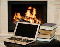 Laptop en stapel van boeken tegen de achtergrond van de open haard royalty-vrije stock foto