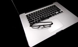 Laptop with eyeglasses on top Royalty Free Stock Photography