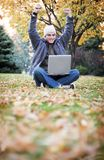 Laptop in the fall. Young student sits outside in the fall air with his laptop Stock Images