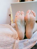 Laptop and feet. Girl sitting on bed with laptop. Feet are in foreground royalty free stock images