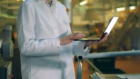Laptop in the female hands of a plant worker. 4K stock footage