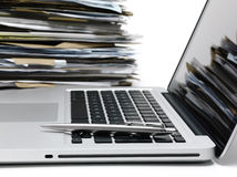 Laptop with files. Laptop with a pile of files in background Royalty Free Stock Photography
