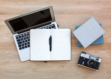 Laptop, Filmkamera, Notizblock mit Stift und ein paar Bücher auf dem Holztisch arbeit Lizenzfreie Stockfotos