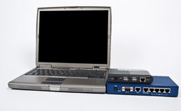 Laptop and firewall with ethernet switch on white Royalty Free Stock Photography