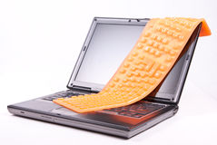 Laptop and flexible orange keyboard Stock Photos
