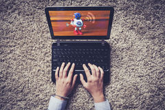 Laptop on the floor. Woman hands typing on the keyboard. Wifi co royalty free stock photography