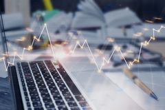 Laptop with forex chart. Close up of office workplace with supplies, laptop and forex chart. Fund management and profit concept. Double exposure Stock Photo