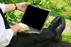 With laptop in garden Stock Images