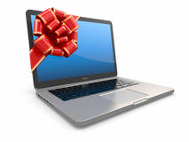 Laptop gift. Bow and ribbon on screen Royalty Free Stock Images