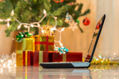 Laptop with gift box and christmas lights Stock Image