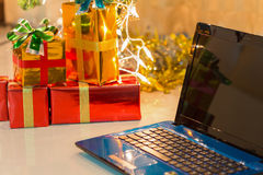 Laptop with gift box and christmas lights Royalty Free Stock Photography