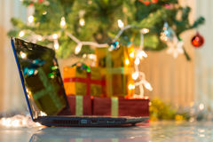 Laptop with gift box and christmas lights Royalty Free Stock Images