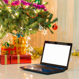 Laptop with gift box and christmas lights Stock Photos