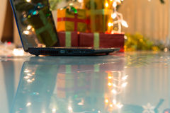Laptop with gift box and christmas lights Stock Images