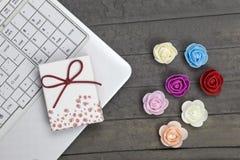 Laptop, giftdoos en zeven rozen op houten raad stock foto's