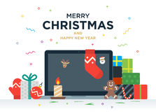 Laptop with gifts, candles, red ball and Christmas. Socks on the screen. Christmas postcard with greeting text Royalty Free Stock Photo