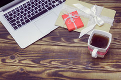 Laptop, gifts and a cup of coffee on a wooden background Stock Image