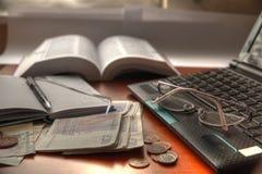 Laptop, Gläser, Notizbuch und Geld. Lizenzfreie Stockfotografie