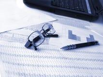 Laptop, Gläser und Feder auf Finanzdokumenten.