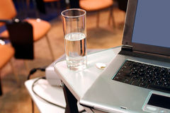 Laptop with glass on presentation. Laptop with gray lcd on presentation. Glass with water near laptop Royalty Free Stock Photography