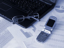 Laptop, glasses and mobile phone. On financial documents. Toned blue. Shallow DOF Stock Photo