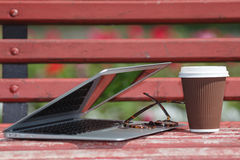 Laptop with Glasses and Notebook Lying on Bench in City Park, Outdoor Study or Internet Freelance Working Concept Royalty Free Stock Photo
