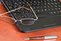 Laptop, glasses and pen Royalty Free Stock Photo