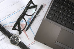 Laptop, glasses, watch, and informational charts Stock Photography